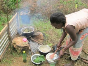 woman cooking over a wood fire