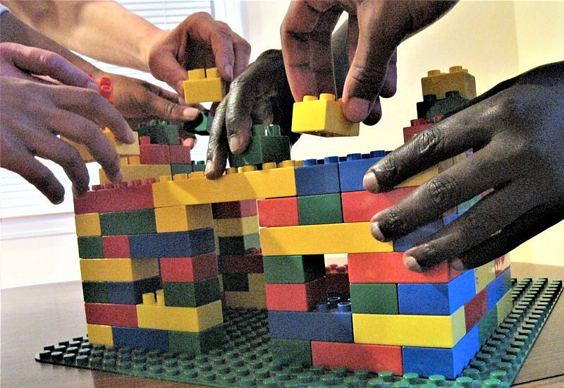 many hands working together to build house with legos