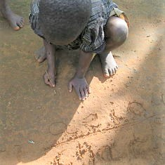 child writing in the dirt