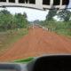 red dirt road full of school children