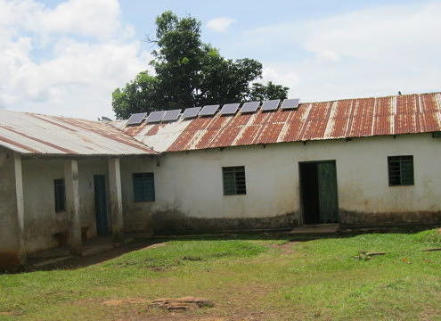 simple white cement building with nine solar panels on rusted tin roof