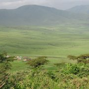 rolling green hills with cluster of village huts