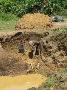 man digging clay for bricks