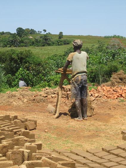 man molding individual clay bricks