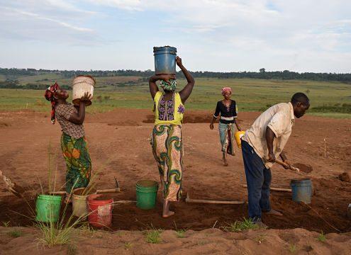 village women moving dirt on soccer field